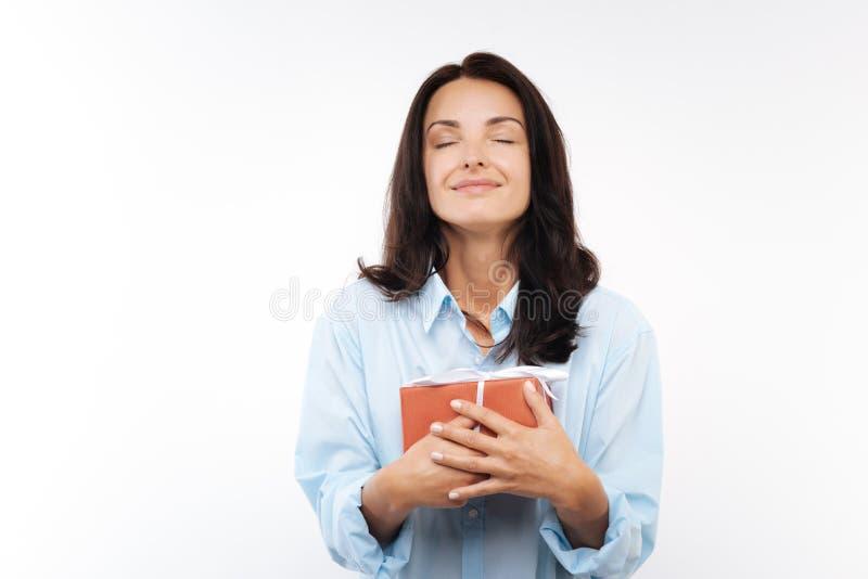 Giovane donna felice che preme il contenitore di regalo al suo petto immagini stock libere da diritti