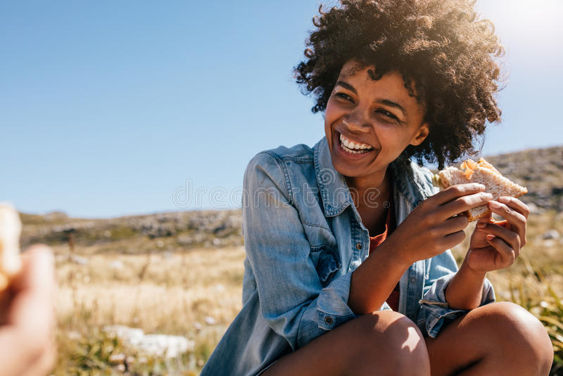 Giovane donna felice che prende rottura durante l'aumento del paese immagini stock
