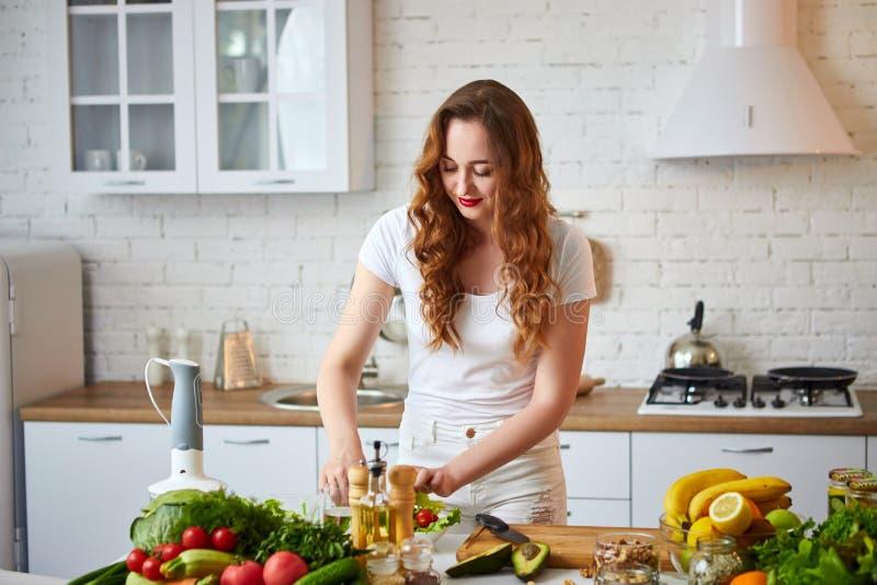 Giovane donna felice che prepara insalata saporita nella bella cucina con gli ingredienti freschi verdi all'interno Alimento sano fotografie stock libere da diritti