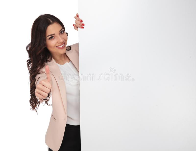 Giovane donna felice che raccomanda l'annuncio che mostra immagine stock