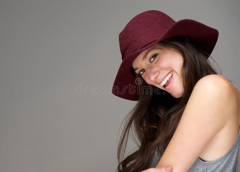 Giovane donna felice che ride con un cappello rosso fotografia stock