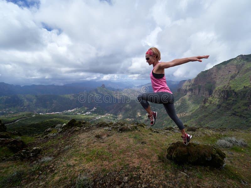 Giovane donna felice che salta sopra la montagna immagini stock
