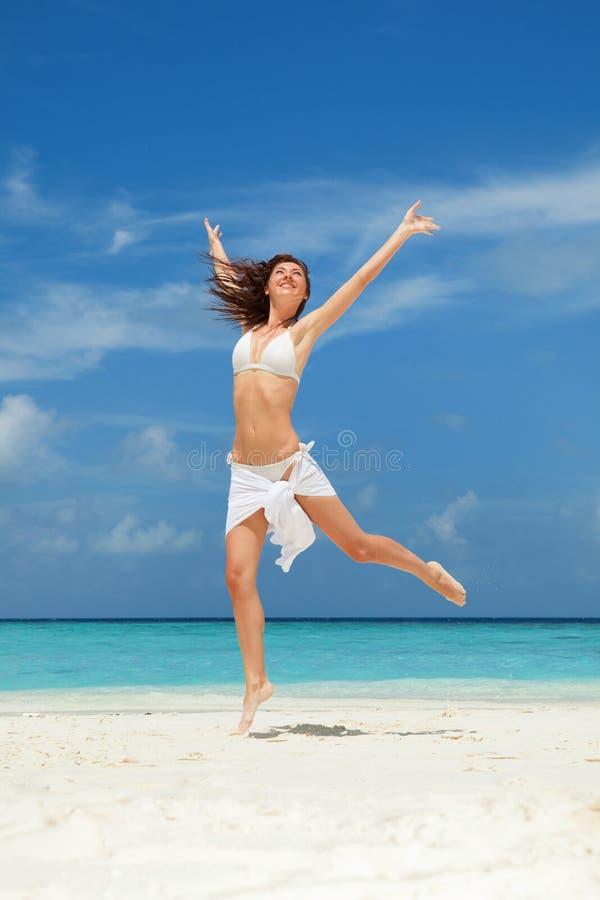 Giovane donna felice che salta sulla spiaggia Mare bianco della sabbia, del cielo blu e del cristallo della spiaggia tropicale va fotografia stock libera da diritti