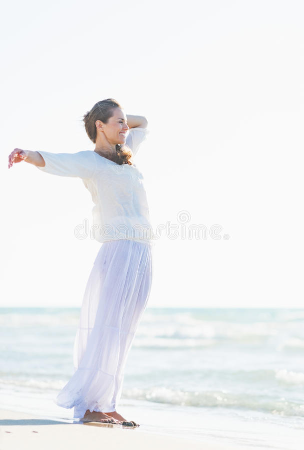 Giovane donna felice che si rilassa alla spiaggia fotografia stock