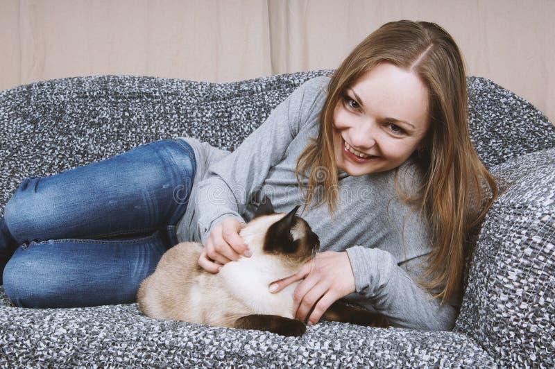 Giovane donna felice che si rilassa sullo strato con il gatto fotografia stock libera da diritti