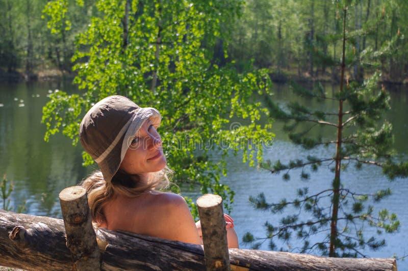 Giovane donna felice che si siede all'aperto sul banco davanti ad un lago con seaview fotografia stock libera da diritti