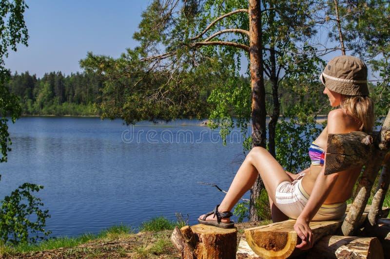 Giovane donna felice che si siede all'aperto sul banco davanti ad un lago con seaview fotografia stock