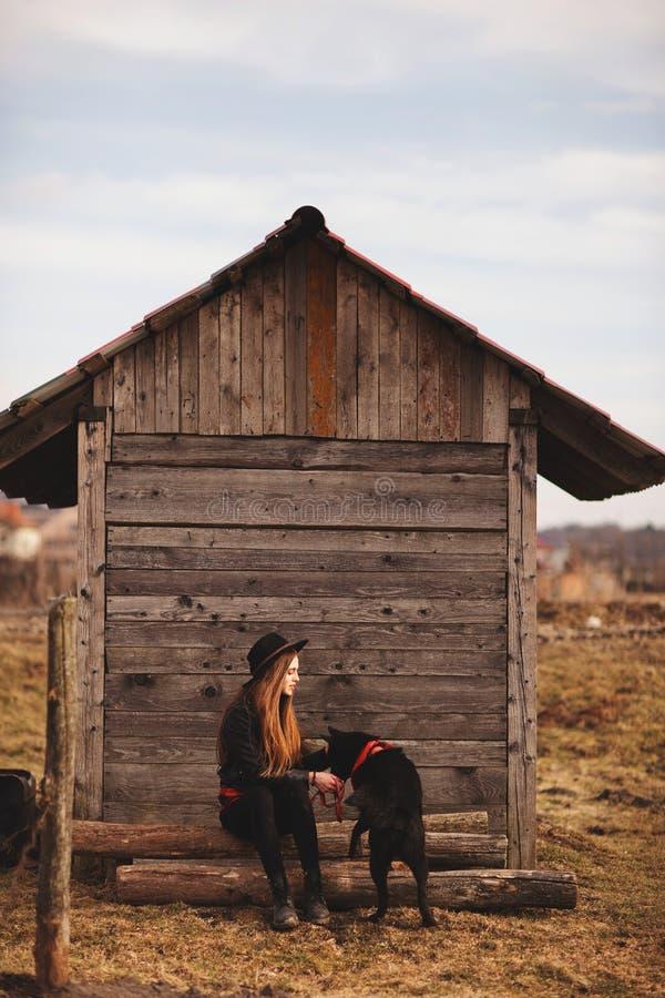 Giovane donna felice che si siede con il suo cane nero nel fron di vecchia casa di legno fotografia stock libera da diritti