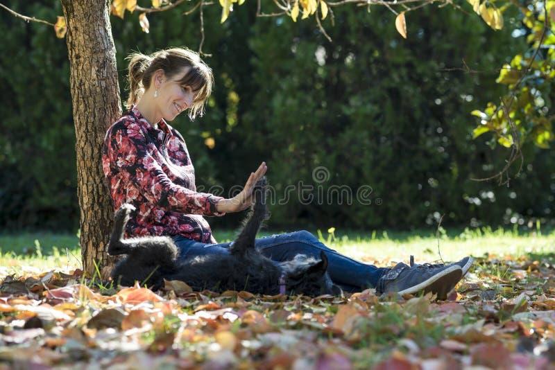Giovane donna felice che si siede sotto un albero in un parco che gioca con He immagine stock