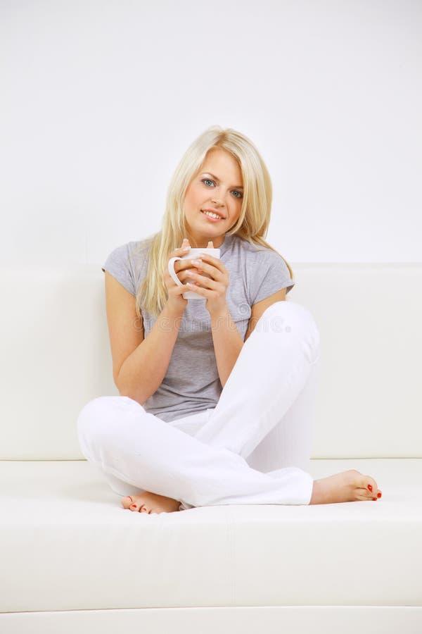 Giovane donna felice che si siede sul sofà, tenente caffè fotografie stock libere da diritti