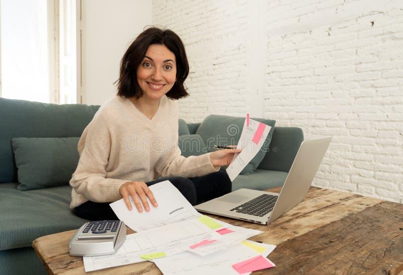 Giovane donna felice che si siede sul sof? circondato dalle carte che calcolano le spese e le fatture di pagamento fotografia stock libera da diritti