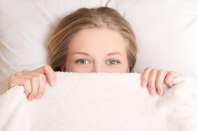 Giovane donna felice che si trova a letto sotto la coperta immagine stock libera da diritti