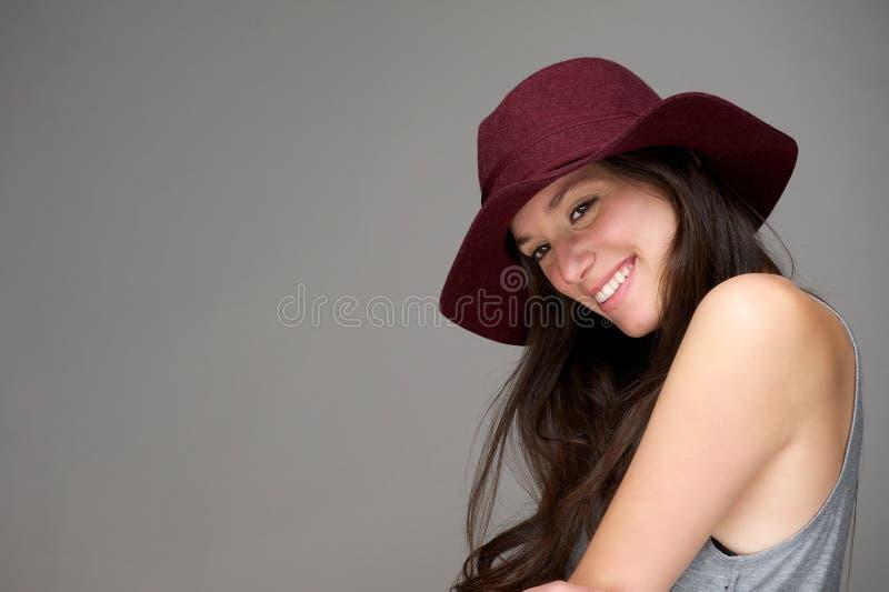 Giovane donna felice che sorride con il cappello rosso immagine stock
