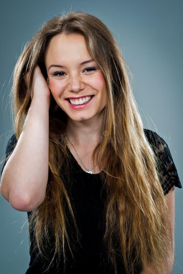 Giovane donna felice che sorride e che tocca i suoi capelli fotografie stock libere da diritti