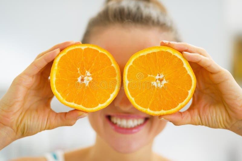 Giovane donna felice che tiene due fette di arancia immagini stock libere da diritti