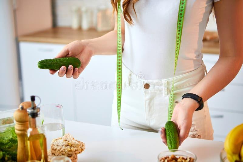 Giovane donna felice che tiene i cetrioli per produrre insalata nella bella cucina con gli ingredienti freschi verdi all'interno  immagini stock libere da diritti