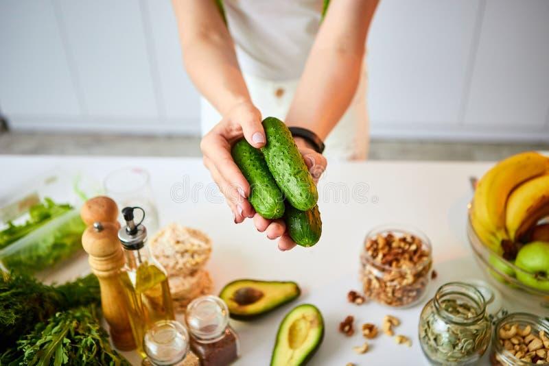 Giovane donna felice che tiene i cetrioli per produrre insalata nella bella cucina con gli ingredienti freschi verdi all'interno  fotografia stock