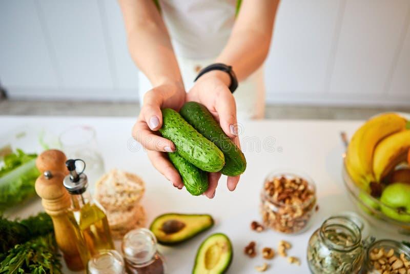 Giovane donna felice che tiene i cetrioli per produrre insalata nella bella cucina con gli ingredienti freschi verdi all'interno  immagini stock