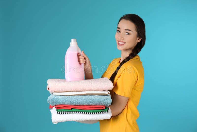 Giovane donna felice che tiene i vestiti ed il detersivo di lavanderia puliti immagine stock