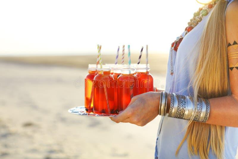 Giovane donna felice che tiene un piatto con bevande al partito di estate immagine stock libera da diritti