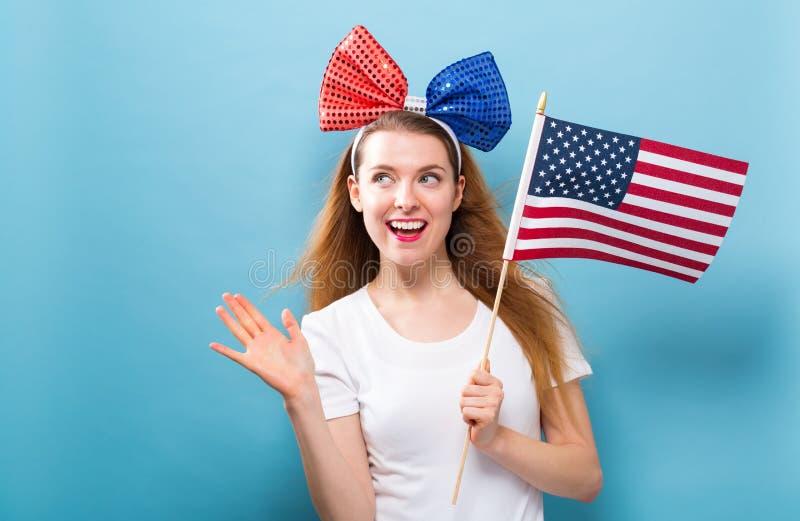 Giovane donna felice che tiene una bandiera americana fotografie stock libere da diritti