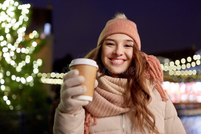 Giovane donna felice con caffè al mercato di natale immagine stock