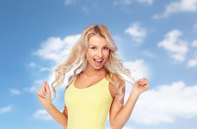 Giovane donna felice con capelli biondi sopra cielo blu immagine stock