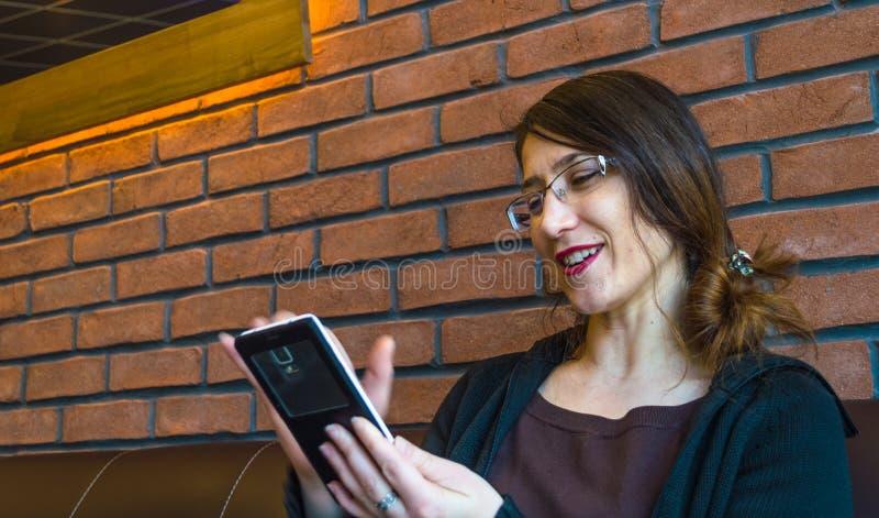 Giovane donna felice con capelli lunghi che gode del suo smartphone fotografie stock