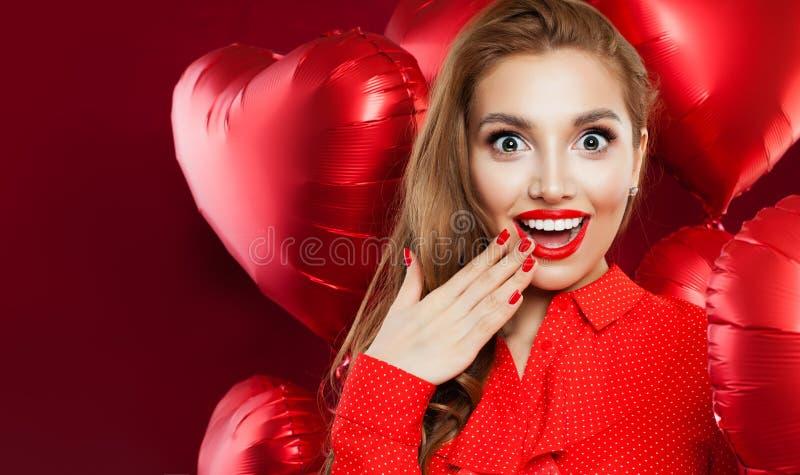 Giovane donna felice con i palloni del cuore su fondo rosso Ha sorpreso la ragazza con trucco rosso delle labbra ed ha aperto la  fotografie stock libere da diritti