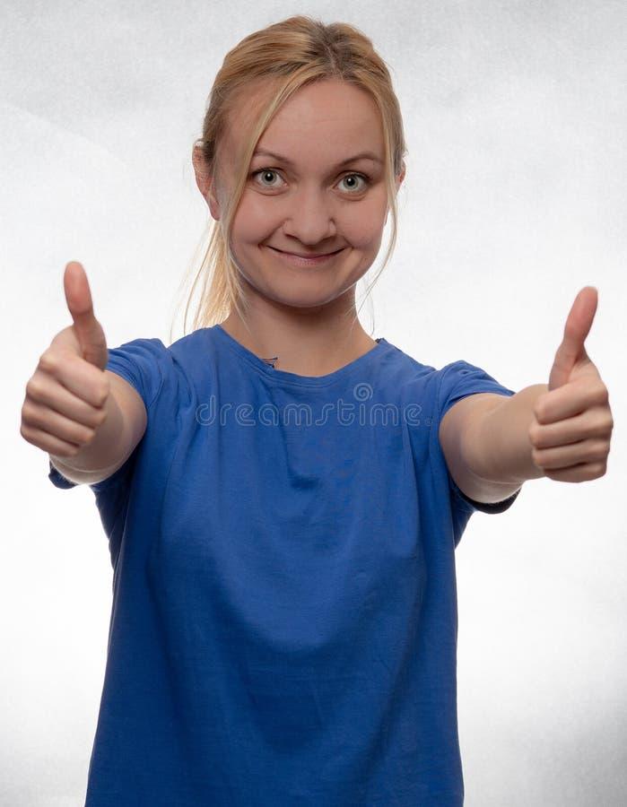 Giovane donna felice con i pollici su in camicia blu casuale immagini stock