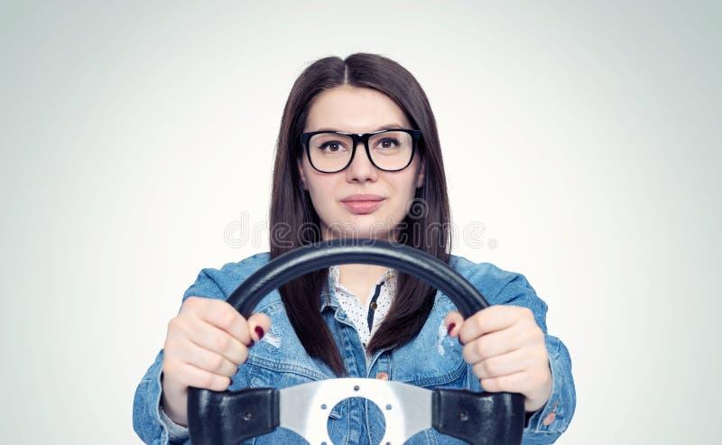 Giovane donna felice con i vetri ed il volante dell'automobile, vista frontale, concetto automatico fotografia stock