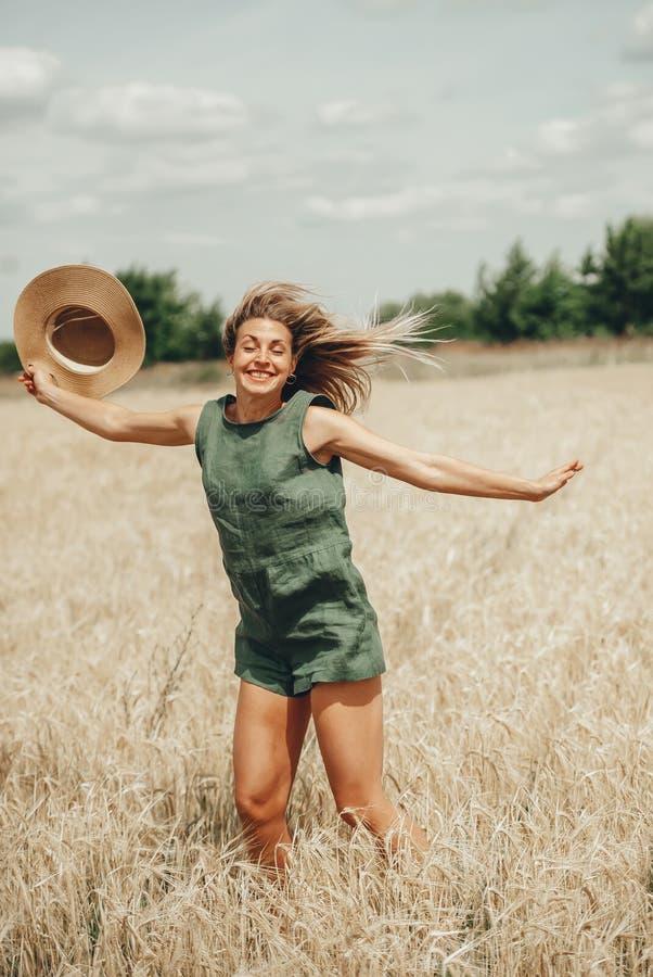 Giovane donna felice con il cappello di paglia in mani che gode del sole sul giacimento di cereale fotografia stock