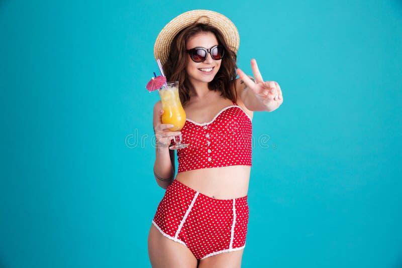 Giovane donna felice con il cocktail che mostra gesto di pace immagini stock libere da diritti