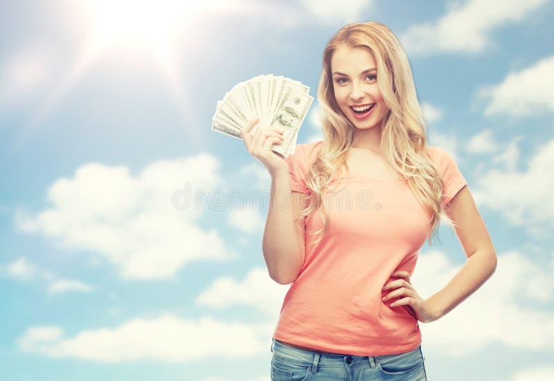 Giovane donna felice con il denaro contante del dollaro degli S.U.A. fotografia stock libera da diritti