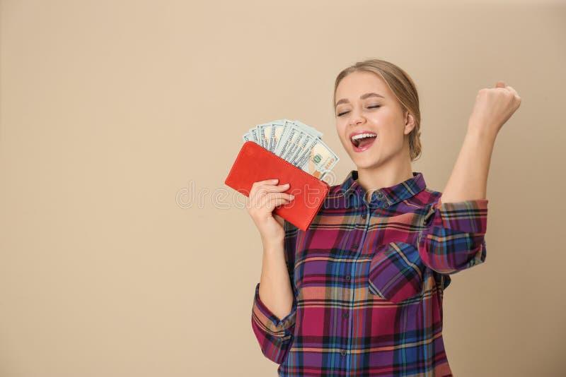 Giovane donna felice con il portafoglio in pieno di soldi sul fondo di colore fotografie stock