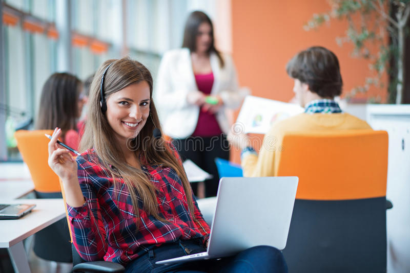 Giovane donna felice con il suo personale, gruppo di affari della gente nel fondo all'ufficio luminoso moderno all'interno fotografia stock