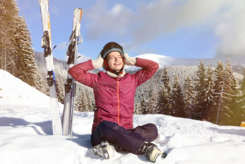 Giovane donna felice con l'attrezzatura dello sci che si siede sulla neve in montagne fotografie stock libere da diritti