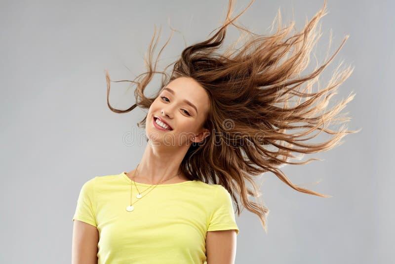 Giovane donna felice con l'ondeggiamento dei capelli lunghi fotografia stock libera da diritti