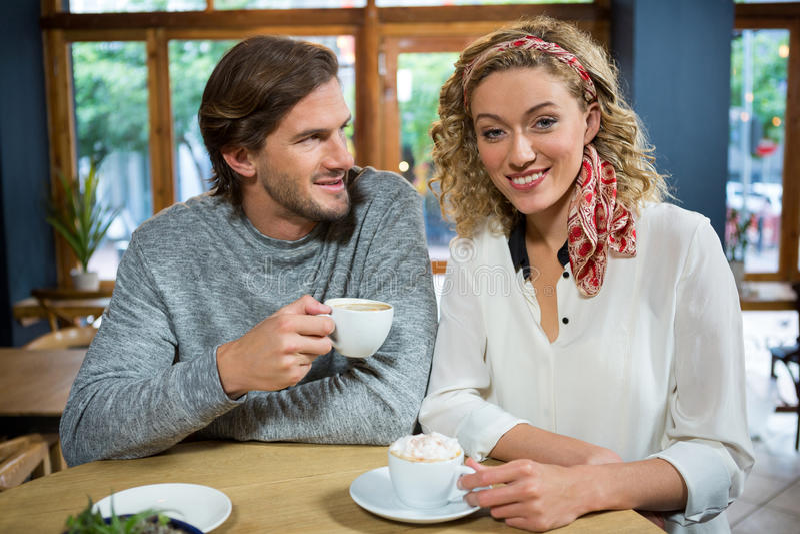 Giovane donna felice con l'uomo alla tavola in caffetteria immagini stock