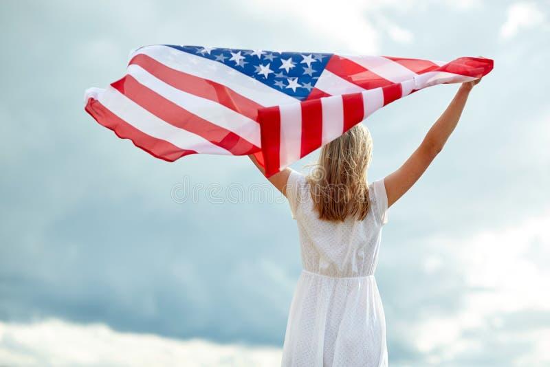 Giovane donna felice con la bandiera americana all'aperto immagine stock