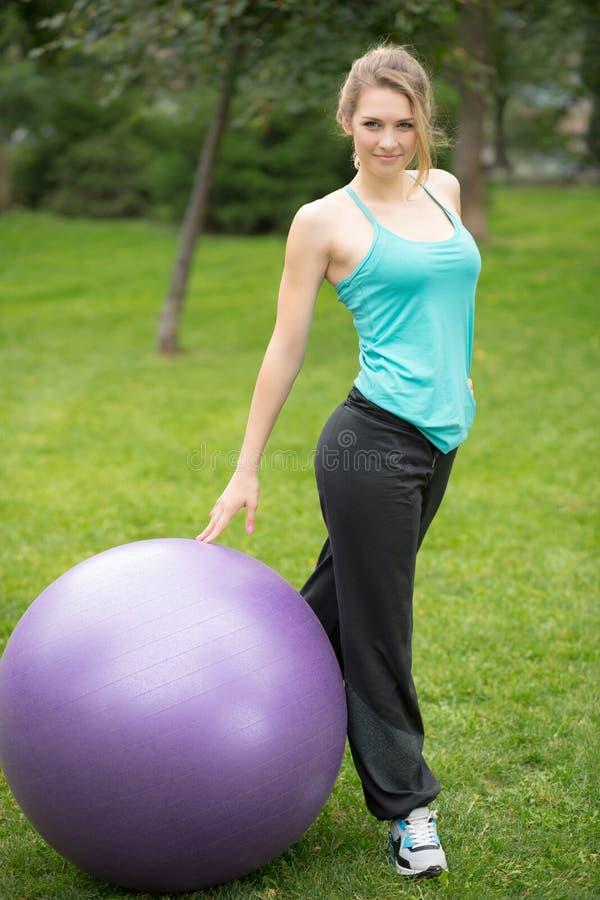Giovane donna felice con la palla di forma fisica, all'aperto fotografie stock libere da diritti