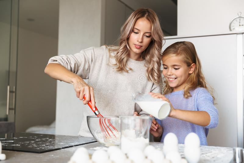 Giovane donna felice con la sua cucina della sorellina all'interno a casa che cucina con la farina e le uova con latte immagine stock libera da diritti
