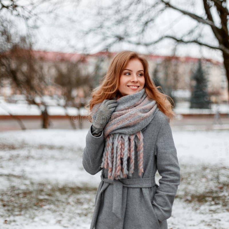 Giovane donna felice con un sorriso sveglio in guanti caldi in un cappotto alla moda di inverno con una posa d'annata tricottata  fotografia stock libera da diritti