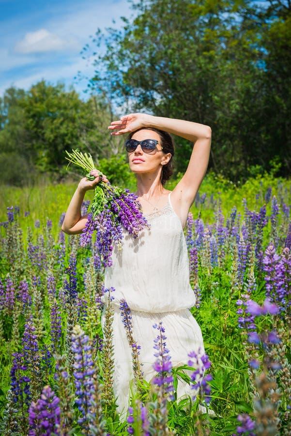 Giovane donna, felice, condizione fra il campo dei lupini viola, sorridendo, fiori porpora Cielo blu sui precedenti Estate, con immagine stock