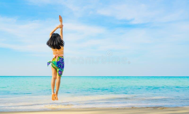 Giovane donna felice in costume da bagno che salta alla spiaggia di sabbia Rilassandosi e godendo della festa alla spiaggia tropi fotografia stock