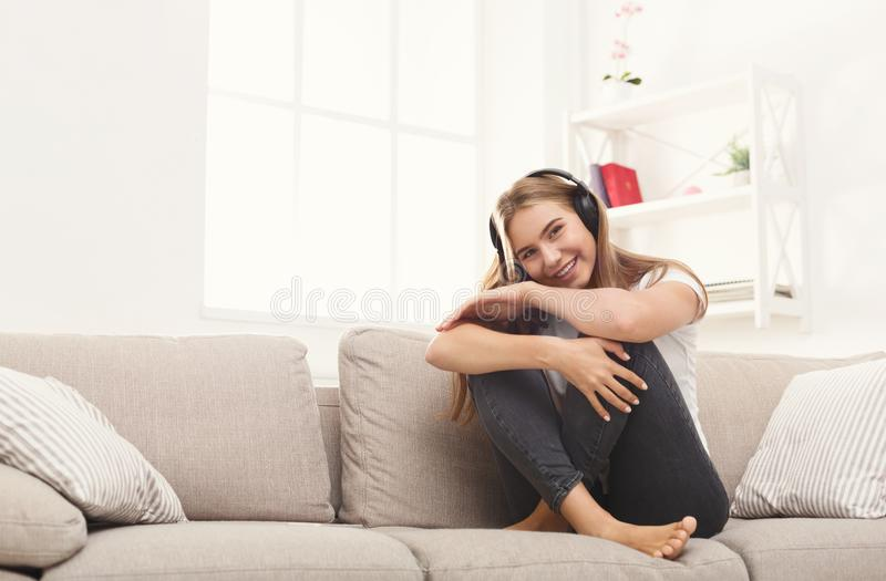 Giovane donna felice in cuffie sullo strato beige fotografia stock libera da diritti