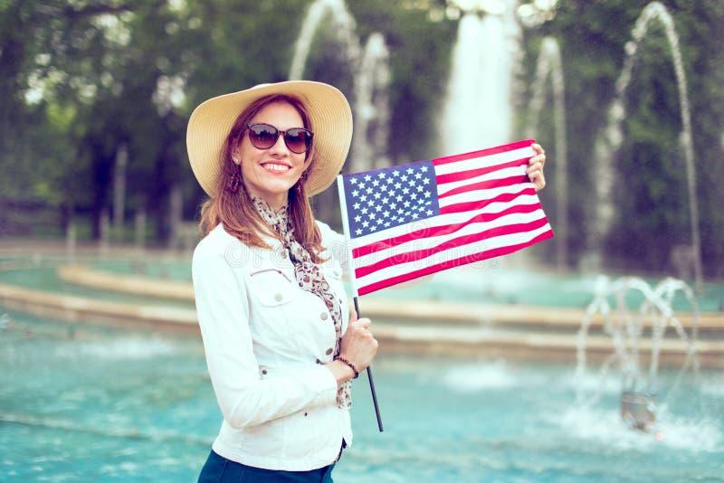 Giovane donna felice del patriota in cappello che allunga la bandiera di U.S.A. in parco fotografie stock libere da diritti