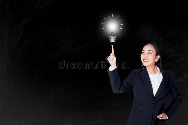 Giovane donna felice di affari che indica lampadina con il concetto di idea e di ispirazione fotografie stock libere da diritti