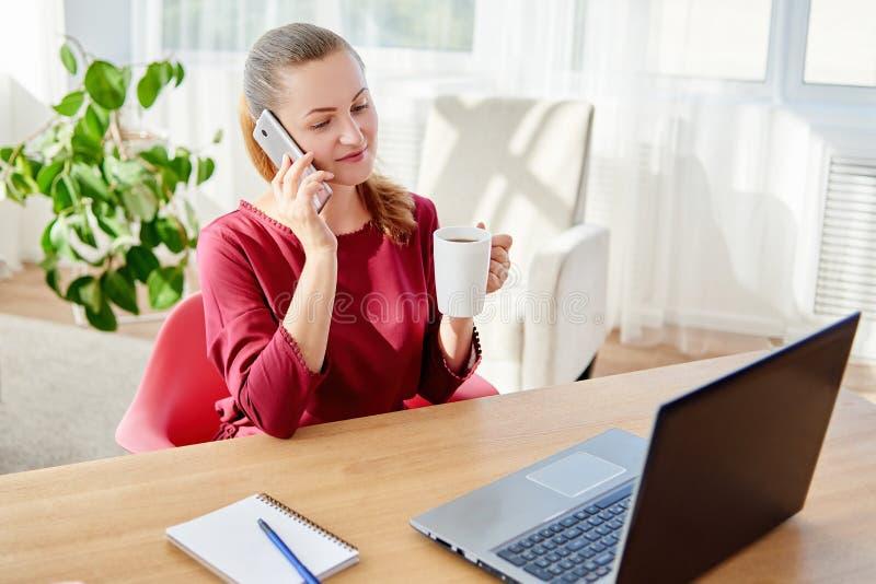 Giovane donna felice di affari che si siede allo scrittorio di legno, godente del caffè e parlante sul cellulare in ufficio moder fotografia stock libera da diritti