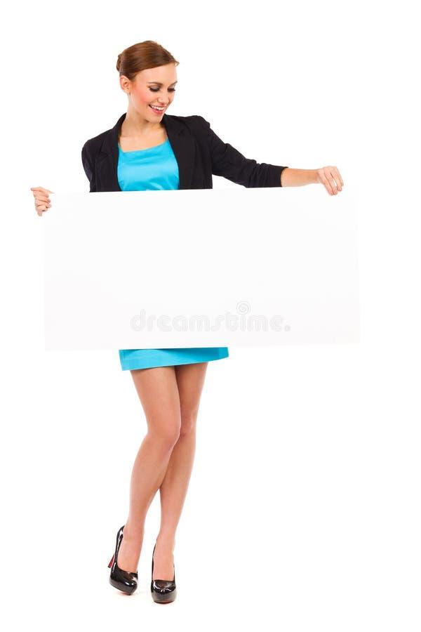 Giovane donna felice di affari che tiene insegna bianca. fotografia stock